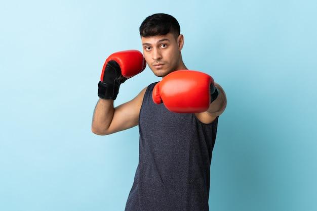 Jonge colombiaanse man geïsoleerd op blauw met bokshandschoenen