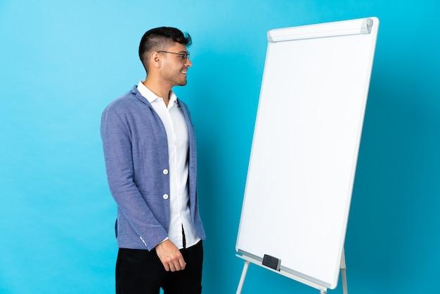 Jonge colombiaanse man geïsoleerd op blauw met een presentatie op wit bord en op zoek naar kant