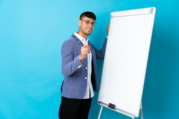 Jonge colombiaanse man geïsoleerd op blauw met een presentatie op wit bord
