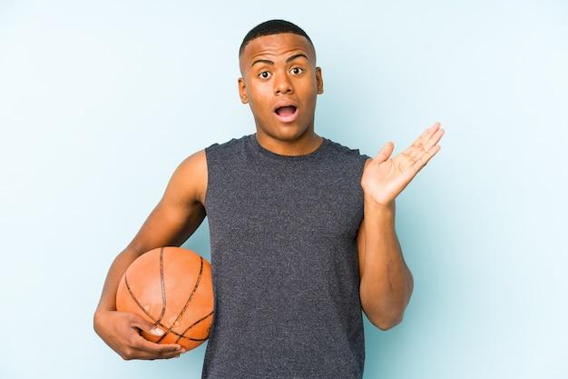 Jonge colombiaanse man met basketbal geïsoleerd verrast en geschokt.
