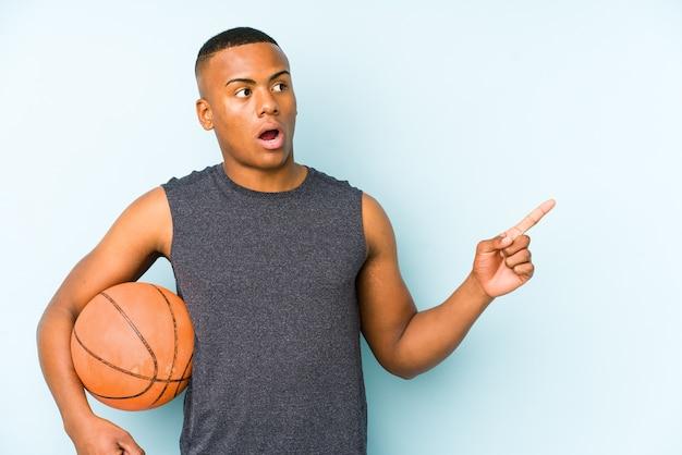 Jonge colombiaanse man met basketbal geïsoleerd wijzend naar de zijkant