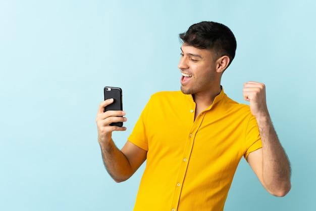 Jonge colombiaanse man met behulp van mobiele telefoon geïsoleerd op blauw een overwinning vieren