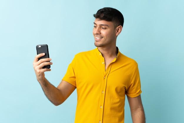 Jonge colombiaanse man met behulp van mobiele telefoon geïsoleerd op blauw met gelukkige uitdrukking