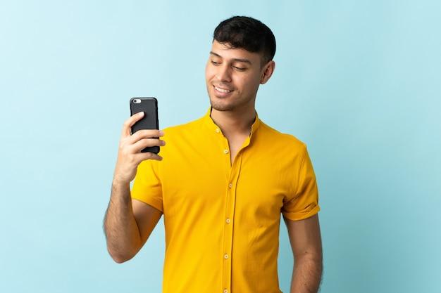 Jonge colombiaanse man met behulp van mobiele telefoon geïsoleerd op blauwe achtergrond met gelukkige uitdrukking