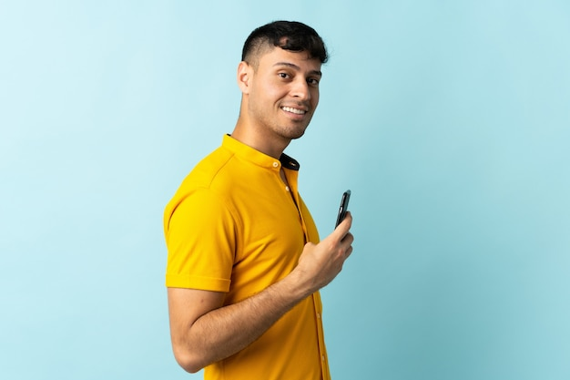 Jonge colombiaanse man met behulp van mobiele telefoon geïsoleerd op blauwe glimlachen