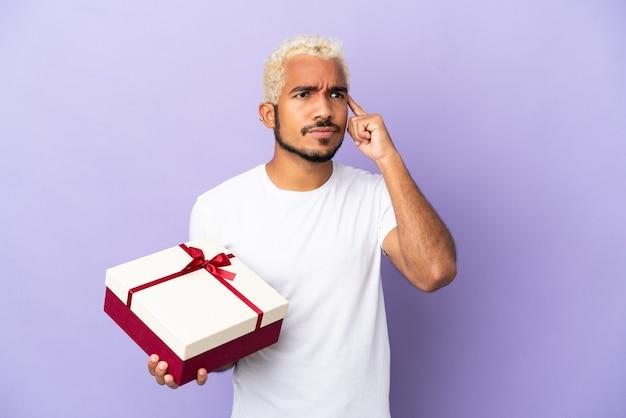 Jonge colombiaanse man met een geschenk geïsoleerd op een paarse achtergrond met twijfels en denken