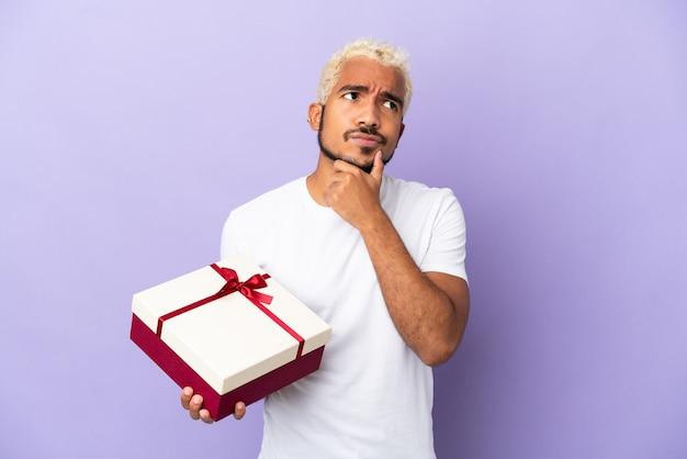 Jonge colombiaanse man met een geschenk geïsoleerd op een paarse achtergrond met twijfels
