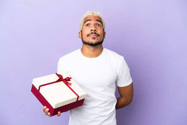 Jonge colombiaanse man met een geschenk geïsoleerd op paarse achtergrond en opzoeken