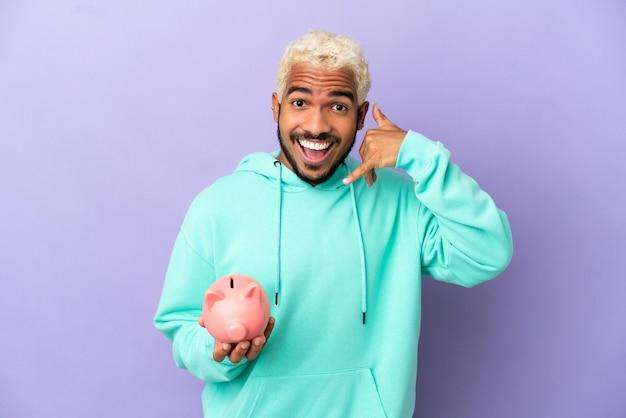 Jonge colombiaanse man met een spaarpot geïsoleerd op paarse achtergrond telefoon gebaar maken. bel me terug teken