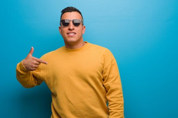 Jonge colombiaanse man persoon wijst met de hand naar een shirt-exemplaar, trots en zelfverzekerd