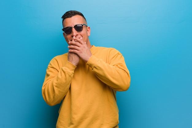 Jonge columbiaanse mens die over iets lacht, die mond behandelt met handen