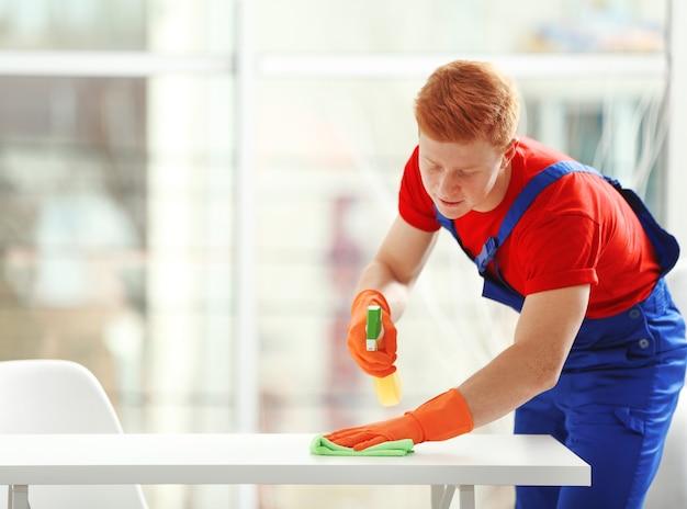 Jonge conciërge met vloeibaar wasmiddel reinigingstafel in kantoor