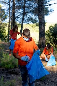 Jonge conciërges die in het bos werken die vuilnis verzamelen.