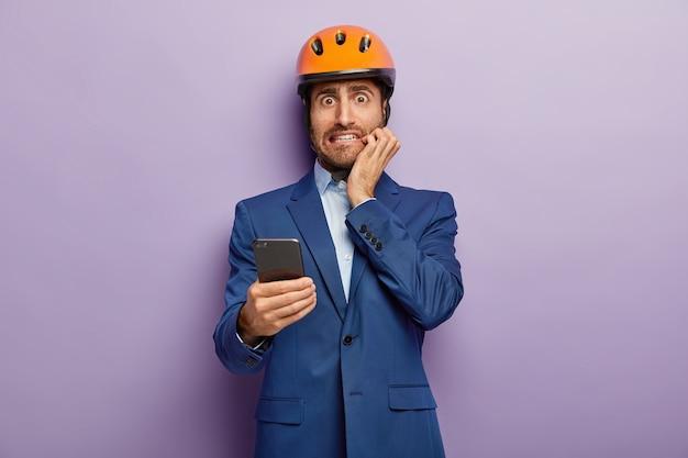 Jonge constructeur of architect draagt een veiligheidshelm, gebruikt een mobiele telefoon en kijkt verlegen