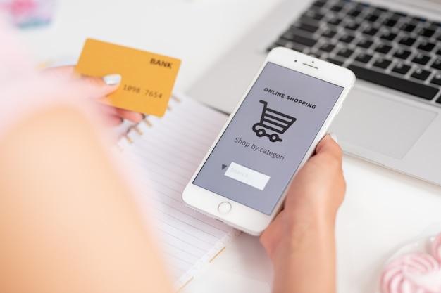 Jonge consument van online winkel met smartphone en bankkaart die goederen in het net zoekt terwijl hij bestelling gaat plaatsen