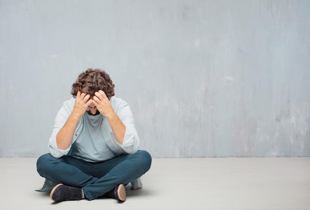 Jonge cool bebaarde man zittend op de vloer. grunge muur achtergrond