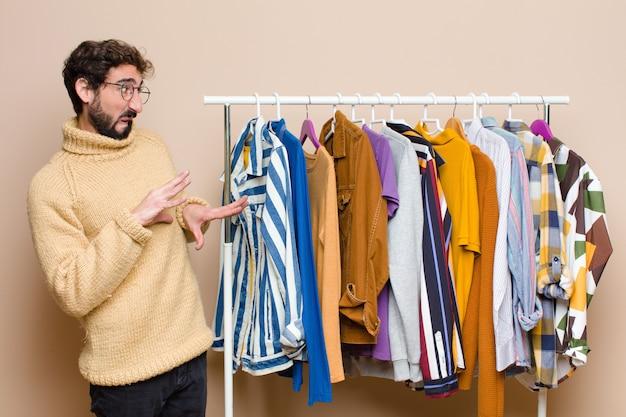 Jonge cool berded man met kleren op vlakke muur