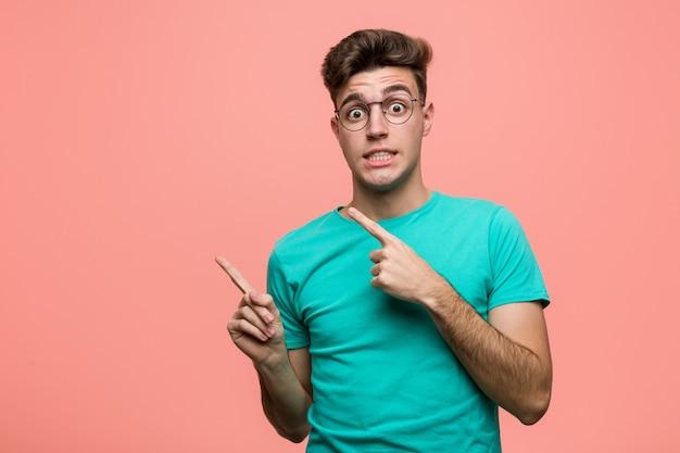 Jonge cool blanke man geschokt wijzend met wijsvingers naar een kopie.