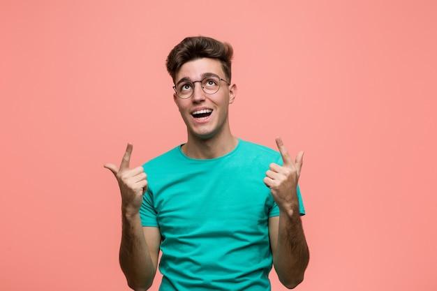 Jonge coole blanke man geeft aan met beide vingers omhoog met een lege ruimte.