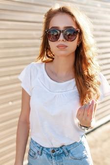 Jonge coole hipster vrouw in stijlvolle zonnebril in een modieus wit t-shirt in trendy spijkerbroek staat in de buurt van een houten vintage muur op een zonnige zomerdag