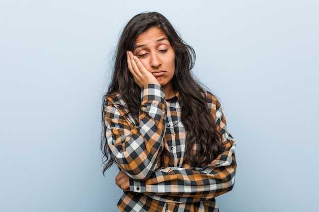 Jonge coole indiase vrouw die zich verveelt, moe is en een relaxdag nodig heeft.