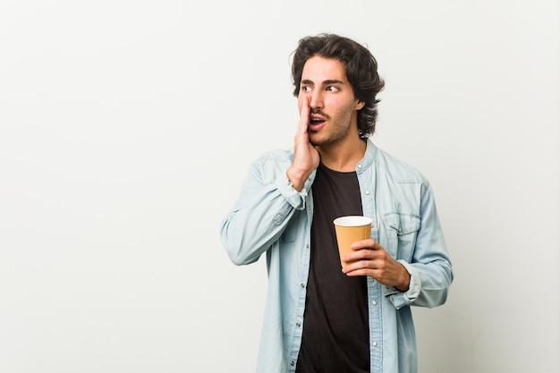 Jonge coole man die een kop koffie drinkt, zegt een geheim heet remnieuws en kijkt opzij