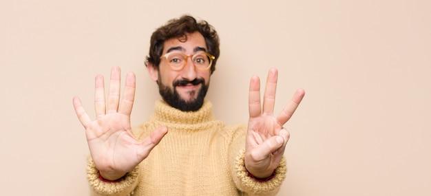 Jonge coole man die vriendelijk glimlacht en kijkt, nummer acht of achtste met de hand naar voren toont, aftellend tegen een vlakke muur