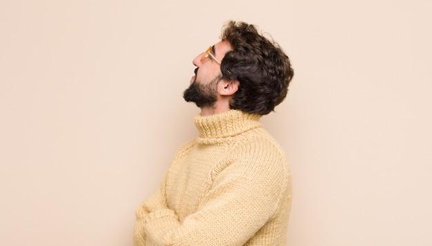 Jonge coole man die zich gelukkig, trots en hoopvol voelt, zich afvraagt of denkt, omhoog kijkt om ruimte te kopiëren met gekruiste armen tegen een vlakke muur