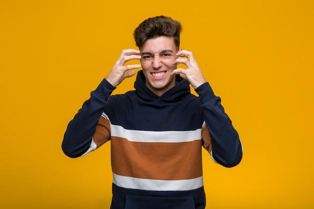 Jonge coole man draagt een hoodie boos schreeuwen met gespannen handen.