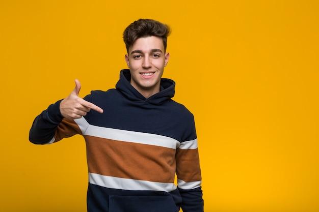 Jonge coole man draagt een hoodie persoon met de hand te wijzen naar een shirt kopie ruimte, trots en zelfverzekerd