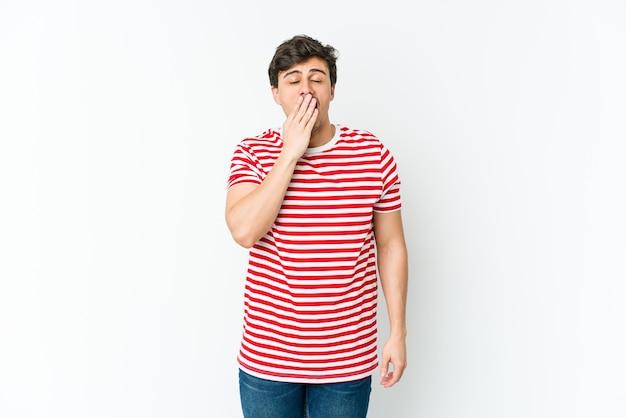Jonge coole man geeuwt met een moe gebaar dat mond bedekt met hand.