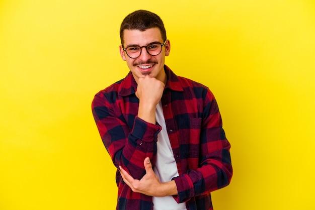 Jonge coole man geïsoleerd op gele muur glimlachend gelukkig en zelfverzekerd, kin met hand aanraken