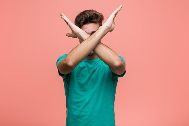 Jonge coole man houdt twee armen gekruist