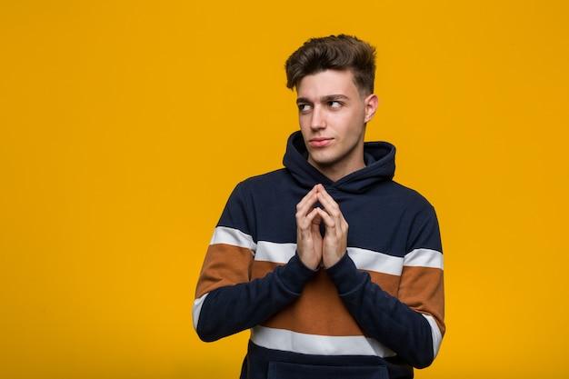 Jonge coole man met een hoodie die een plan bedenkt en een idee opstelt.