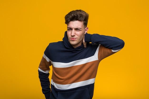 Jonge coole man met een hoodie die leed aan nekpijn vanwege een zittende levensstijl.