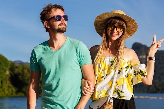Jonge coole paar poseren in de buurt van meer op romantische vakantie, heldere stijlvolle zomeroutfits.
