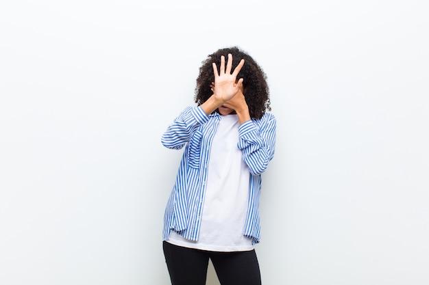 Jonge coole vrouw die gezicht bedekt met de hand en andere hand vooraan zet om de camera te stoppen, weigert foto's of foto's