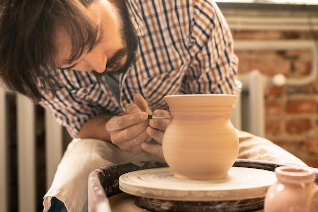 Jonge creatieve ambachtsman met penseelstreep met roze verf terwijl het verfraaien van nieuwe kleipot in workshop