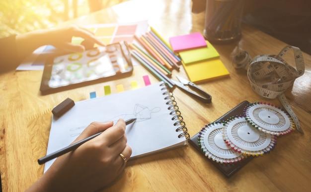 Jonge creatieve atelier modeontwerper werken aan project in een studio