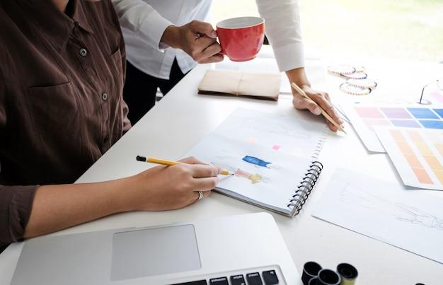 Jonge creatieve kleermakers modeontwerpers team werken brainstormen over project in een studio