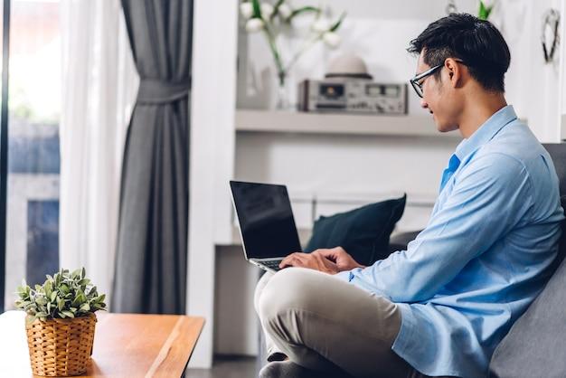 Jonge creatieve lachende gelukkig aziatische man ontspannen met behulp van desktop computer werken en videoconferentie vergadering online chat thuis