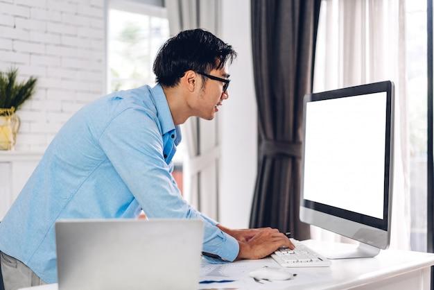 Jonge creatieve man met desktopcomputer op kantoor