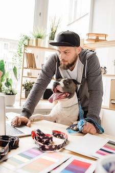 Jonge creatieve mannelijke ontwerper en zijn huisdier die door lijst voor laptop in studio of bureau aan huis werken