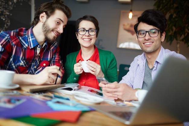 Jonge creatieve mensen kijken naar laptop scherm glimlachen