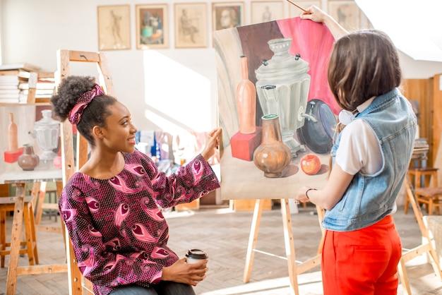 Jonge creatieve multi-etniciteit studenten praten over schilderen tijdens de pauze in de universiteitsstudio om te schilderen