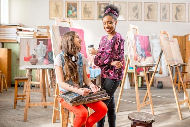 Jonge creatieve multi-etniciteitsstudenten die tijdens de pauze in de universiteitsstudio praten om te schilderen
