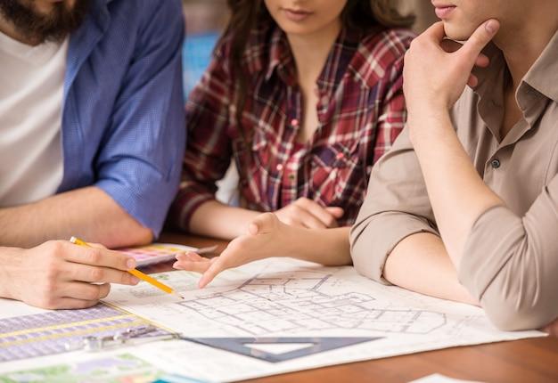 Jonge creatieve ontwerpers werken samen aan project.