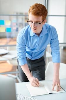 Jonge creatieve student of ontwerper die aantekeningen in voorbeeldenboek maakt terwijl hij naar het computerscherm kijkt