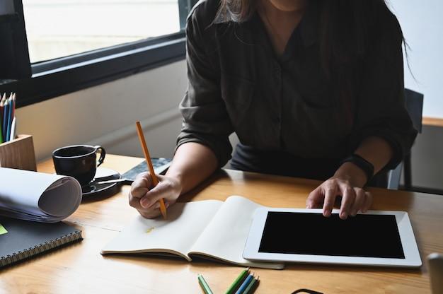Jonge creatieve vrouw die op notitieboekje schrijft en tabletcomputer met behulp van.