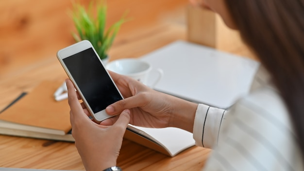 Jonge creatieve vrouw in gestreepte shit terwijl ze haar zwarte smartphone met een leeg scherm vasthoudt aan het moderne houten bureau.